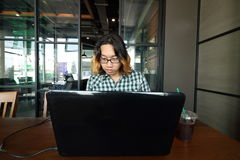 年轻亚裔人广角射击与他的膝上型计算机一起使用在办公室会议室  免版税库存图片