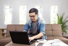 亚裔人微笑和使用膝上型计算机的为工作或sufing的互联网 图库摄影