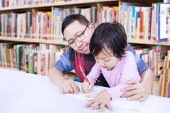 亚裔人教一个女孩在图书馆写 图库摄影