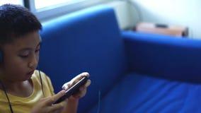 亚裔人是在家看起来与智能手机的空白的billboardHappy孩子戏剧比赛和佩带耳机的旅客 影视素材