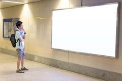 亚裔人是看起来空白的广告牌的旅客 免版税库存照片