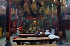 亚裔人民祈祷的和燃烧的香火在塔黏附 免版税图库摄影