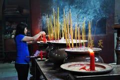 亚裔人民祈祷的和燃烧的香火在塔黏附 免版税库存照片