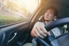 亚裔人男性驱动一辆汽车和看窗口 免版税库存照片