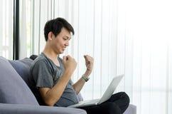 年轻亚裔人递与计算机膝上型计算机的幸福片刻 免版税库存图片