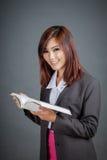 亚裔企业女孩读了书和微笑 免版税图库摄影