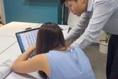 亚裔企业雇员谈论关于关于膝上型计算机的财务数据 免版税库存图片