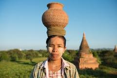 亚裔传统在头的农夫运载的罐画象  免版税库存图片