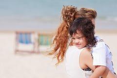 亚裔使用在海滩的妈妈和儿子 免版税图库摄影