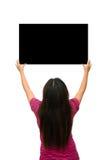 亚裔俏丽的女孩在两手上站立和拿着黑人委员会 库存图片