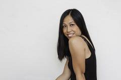 亚裔俏丽的微笑的妇女 免版税图库摄影