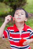 亚裔儿童吹的肥皂泡在夏天公园,自然backgrou 库存图片