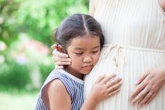 亚裔儿童女孩听的婴孩和拥抱怀孕的母亲 库存图片