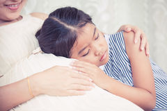亚裔儿童女孩听的婴孩和拥抱怀孕的母亲 库存照片