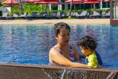 亚裔儿童男孩学会在一游泳场的游泳有妈妈的 图库摄影