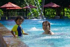 亚裔儿童男孩学会在一游泳场的游泳有妈妈的 免版税库存图片