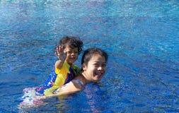 亚裔儿童男孩学会在一游泳场的游泳有妈妈的 - Su 图库摄影