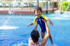 亚裔儿童男孩学会在一游泳场的游泳有妈妈的 - Su 免版税图库摄影
