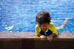 亚裔儿童男孩学会在游泳场的游泳 库存图片