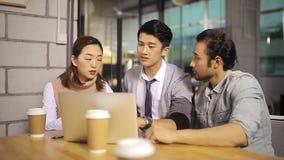 亚裔公司人民谈论事务在办公室
