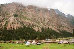亚裔农夫在中亚之间山的一个谷安置Yurts和自动汽车  库存照片
