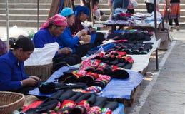 亚裔前辈剪裁缝合和卖五颜六色的传统纺织品 免版税库存图片