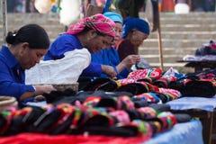 亚裔前辈剪裁缝合和卖五颜六色的传统纺织品 免版税图库摄影