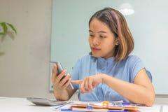 亚裔办公室妇女检查她的在智能手机的短信 免版税库存照片