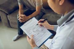 亚裔医生审查身体的反常项目并且诊断在本文的疾病与医疗报告  免版税库存照片