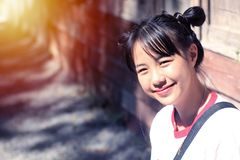 亚裔十几岁的女孩做头发领带,两名安慰者微笑着 免版税库存照片