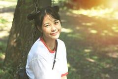 亚裔十几岁的女孩做头发领带,两名安慰者微笑着 库存照片