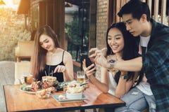 亚裔单身妇女羡慕与做作为selfie的爱夫妇在 免版税库存照片