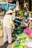 亚裔卖新鲜的苦涩瓜和zucchi的顾客和贸易商 库存图片