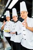 亚裔厨师在旅馆餐馆厨房里 库存照片