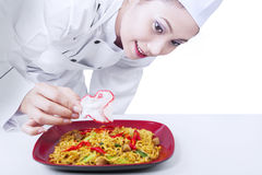亚裔厨师的最后的接触 免版税库存图片