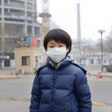 亚裔反对大气污染的男孩佩带的嘴面具 免版税库存照片