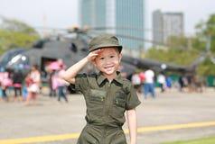 亚裔反对迷离直升机背景的儿童女孩佩带的空军飞行员衣服画象  免版税库存照片