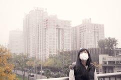 亚裔反对阴霾大气污染2的女孩佩带的嘴面具 免版税库存图片