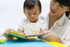 亚裔可爱的婴孩一年为孩子看书 免版税库存图片