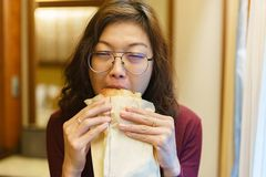 亚裔吃面包碳水化合物的妇女成熟成人 免版税图库摄影
