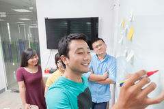 亚裔商人合作在白色墙壁上的图画 免版税库存图片