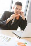 亚裔商人喝咖啡 免版税库存图片