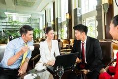 亚裔商人在会议上在旅馆游说 免版税库存照片