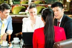 亚裔商人在会议上在旅馆游说 免版税库存图片