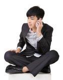 亚裔商人接电话并且坐地面 免版税库存图片