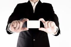 亚裔商人显示在白色背景的一张空白的名片 免版税库存照片