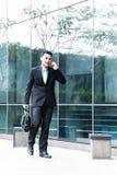 亚裔商人谈话与手机外面 库存照片