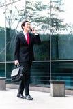 亚裔商人谈话与手机外面 库存图片