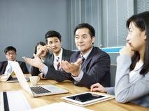 亚裔商人谈话在交涉桌上 免版税库存照片
