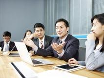 亚裔商人谈话在交涉桌上 库存照片